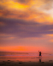 Person Walking On The Beach At Sunset