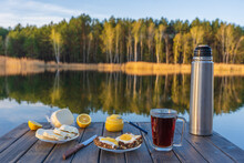 Breakfast With Hot Tea, Cheese Sandwich And Honey On Wooden Table In Morning Next To The Lake. Nature And Food Concept
