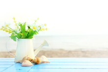 Many Flower In White Watering Vase With Brown Shells On Blue Wooden Table On Blur Sea View , Concept Summer On The Beach, Feeling Soft