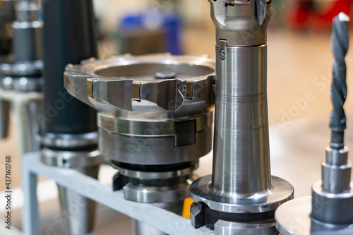Canvas Print Arbors with cutters and drills for a CNC machine on a rack, tools and equipment in a factory and an enterprise