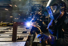 An Electric And Gas Welder In An Electromechanical Workshop Welds A Metal Structure At A Mechanical Assembly Site.
