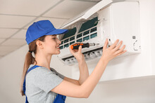 Young Female Electrician Repairing Air Conditioner In Room