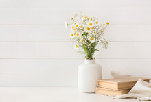 Vase With Beautiful Chamomile Flowers And Books On Light Wooden Background