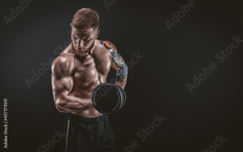 Canvas Young muscular guy pumping biceps with dumbbells