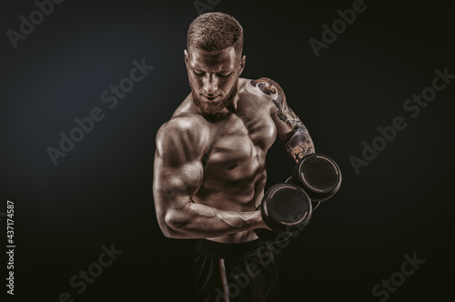 Young muscular guy pumping biceps with dumbbells Fotobehang
