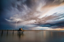 Calm Before The Storm Brewing On Horizon With Menacing Dark Thunder Clouds Over Calm Smooth Waters Of Gironde Estuary With Traditional Fishing Hut In Charente Maritime