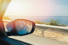 Close-up Of Side Mirror Of The Moving Car With Reflection Of The Sea