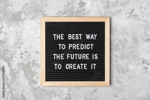 The best way to predict the future is to create it. Motivational quote on black letter board on gray background. Concept inspirational quote of the day. Greeting card, postcard
