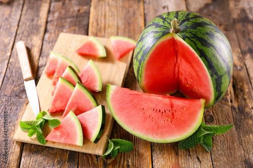 Fototapeta watermelon and cut on wooden board