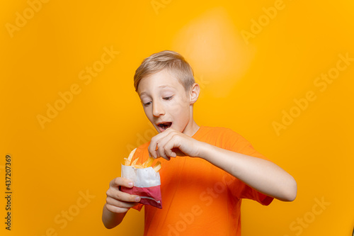 Cuadros en Lienzo a boy in an orange T-shirt holds a bag of deep-fried potatoes in front of him an
