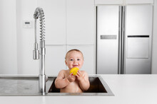 Smiling Baby Taking Bath In Kitchen Sink Holding Rubber Duck