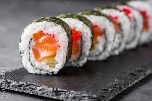 Obraz na płótnie appetizing sushi roll maki with salmon on a black stone plate