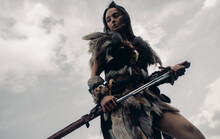 Woman Stands In Image Of Warrior Amazon With Sword In Her Hand.
