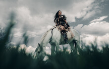 Woman Rides On Horseback In Image Of Warrior Amazon On Grass And Sky Background.