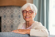 Leinwandbild Motiv Happy senior woman wearing red spectacles at home
