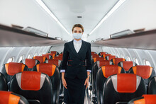 In Mask. Young Stewardess On The Work In The Passanger Airplane
