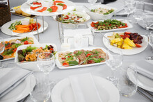 Beautifully Set Table In The Banquet Hall Of The Restaurant. A Table With Appetizers For Wine, Cold Dishes And Salads. White Tablecloths And Napkins