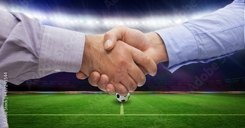 Composition of business people shaking hands over sports stadium