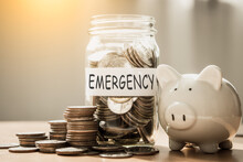 A Lot Coins In Glass Money With Piggy Bank For Saving Emergency Money.Saving For Emergency Concept.