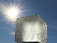 A Roughly Crafted Glass Cube Resembling An Ice Cube Against A Blue Sky And Sun