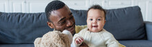 Cheerful Baby Looking At Camera Near African American Father And Teddy Bear, Banner