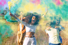 Beautiful Young Man And Woman Hold Light Up Colored Smoke Bombs - Happy Friends Having Fun In The Park With Multicolored Smoke Bombs - Young Students Celebrating Spring Break Together. Holi Festival.