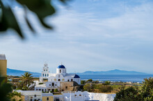 Cityscape Of Traditional Village Karterados On Santorini Island, Greece. Traditional White Architecture. View Of The Greek Orthodox Church With A Blue Domes And Bell Tower.