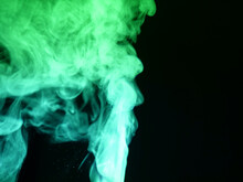 Abstract Colour Series. Composition Of Colourful Smoke In Motion. Fusion Of Neon Green Mist Isolated On A Dark Background To Inspire Creativity.