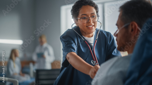 Canvas Hospital Ward: Friendly Black Head Nurse Uses Stethoscope to Listen to Heartbeat and Lungs of Recovering Male Patient Resting in Bed, Does Checkup