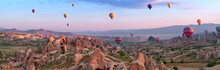 Hot Air Balloons Over Mountain Landscape In Cappadocia, Turkey. Panoramic View At Sunrise