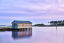 A Boat House On A Creek Just After Sunset With A Purple Sky