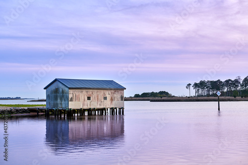 A boat house on a creek just after sunset with a purple sky Fotobehang