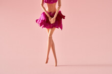 Plastic Woman Figure Dressed In Rose Petals Crossing Legs As If Wanting To Pee Or Having Menstrual Pain