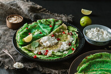 Green Vegan Crepes With Spinach Or Pancakes With Cottage Cheese, Pomegranate, Nuts And Spinach Leaves On Black Plate Over Dark Wooden Background. Healthy Vegan Food, Homemade Breakfast, Close Up