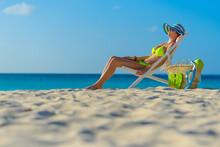 Woman With Bikini And Beach Hat Sitting On Lounge Chair With Beach Bag On The Beach In Aruba