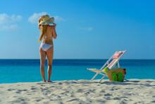 Woman With Bikini And Beach Hat Next To Lounge Chair And Beach Bag On The Beach In Aruba