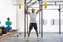 Black Strong Man Lifting Weights In Fitness Center. Physical Training. Space For Text.