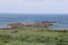 海に細長く続く岩場がある海岸風景