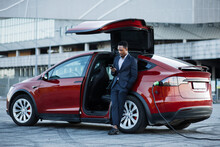 Full Length Portrait Of Successful Businessman In Suit Using Modern Smartphone For Checking Working Emails While Leaning On Red Luxury Car. African Man Waiting While His Electric Car Charging.