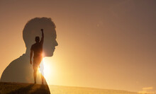 Silhouette Of Strong Young Man Feeling Determined, Empowered And Motivated Putting Fist Up To The Sky. People Power And Inner Strength Concept.