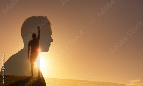 Canvas Print Silhouette of strong young man feeling determined, empowered and motivated putting fist up to the sky