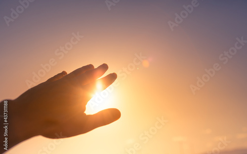 Foto hand reaching out to sky touching the warm sunshine