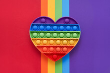 Colorful Trendy Pop It Fidgets Toy On A Rainbow Background. Toy Anti-stress, Simple Dimple. LGBT Concept. Top View