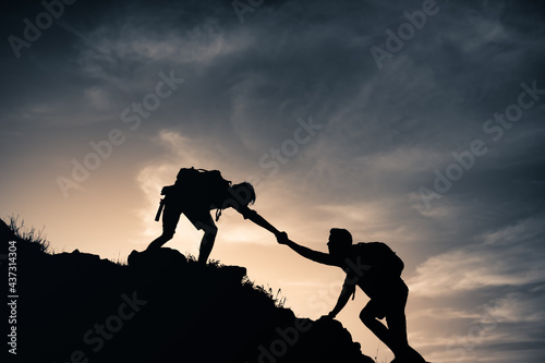 Fotografie, Obraz Mountain combiners helping each other climb up a mountain edge