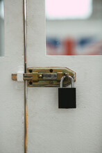 Vertical Shot Of A White Door With Glass And A Black Metal Padlock - For Backgrounds And Textures
