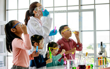Asian Female Scientist Teacher In White Lab Coat Having Fun Playing Blowing Soap Bubbles With Little Innocent Happy Pre-elementary Boy And Girl Children Wears Safety Goggles In School Laboratory