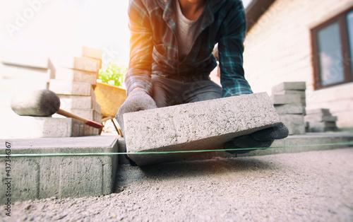 Worker lining paving slabs path Fotobehang