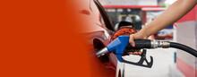 Gas Station Worker's Hand Holding Blue Benzene Gas Pump, Filling Up Orange Sport Car Tank. Close Up