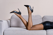 Female Legs On Couch In Faux Leather Dress, Fishnets And Stilettos