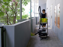 Young Hotel Maid In Blue Uniform Push Housekeeping Cart On The Corridor In Front Of The Hotel Room. The Laundry Basket, Glass Cleaner, Rubber Gloves, Door Mat And Vacuum Cleaner Are On The Cart.